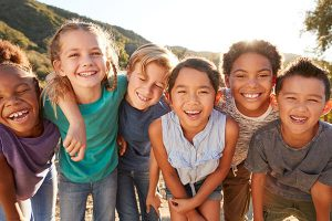 group of children huddled together and smiling outdoors
