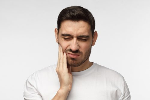 man in white shirt in front of white background holding his face in pain