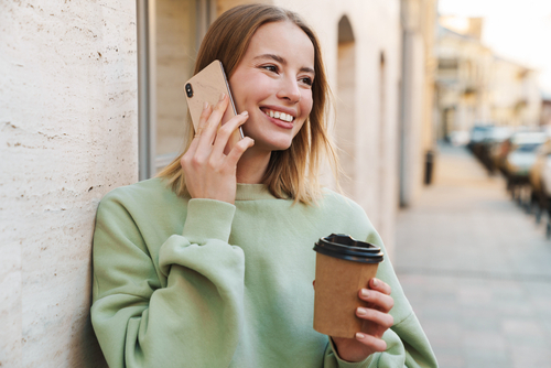young girl on phone smiling and holding coffee cup